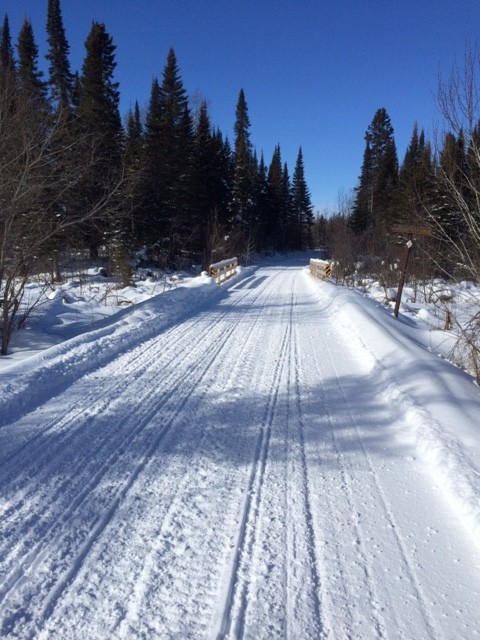 Snowmobile trail over a bridge on a sky blue winter day near spring